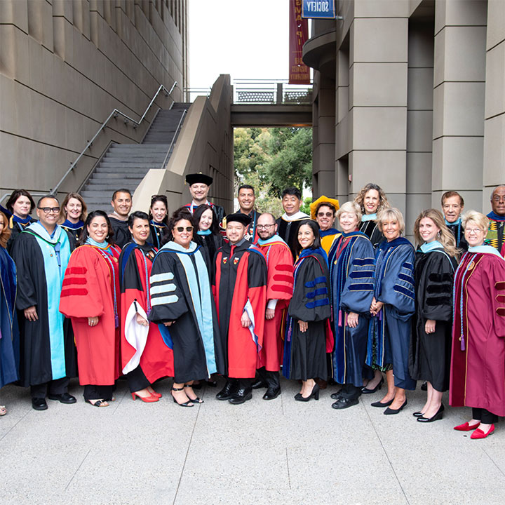 SOE faculty standing together in commencement gowns