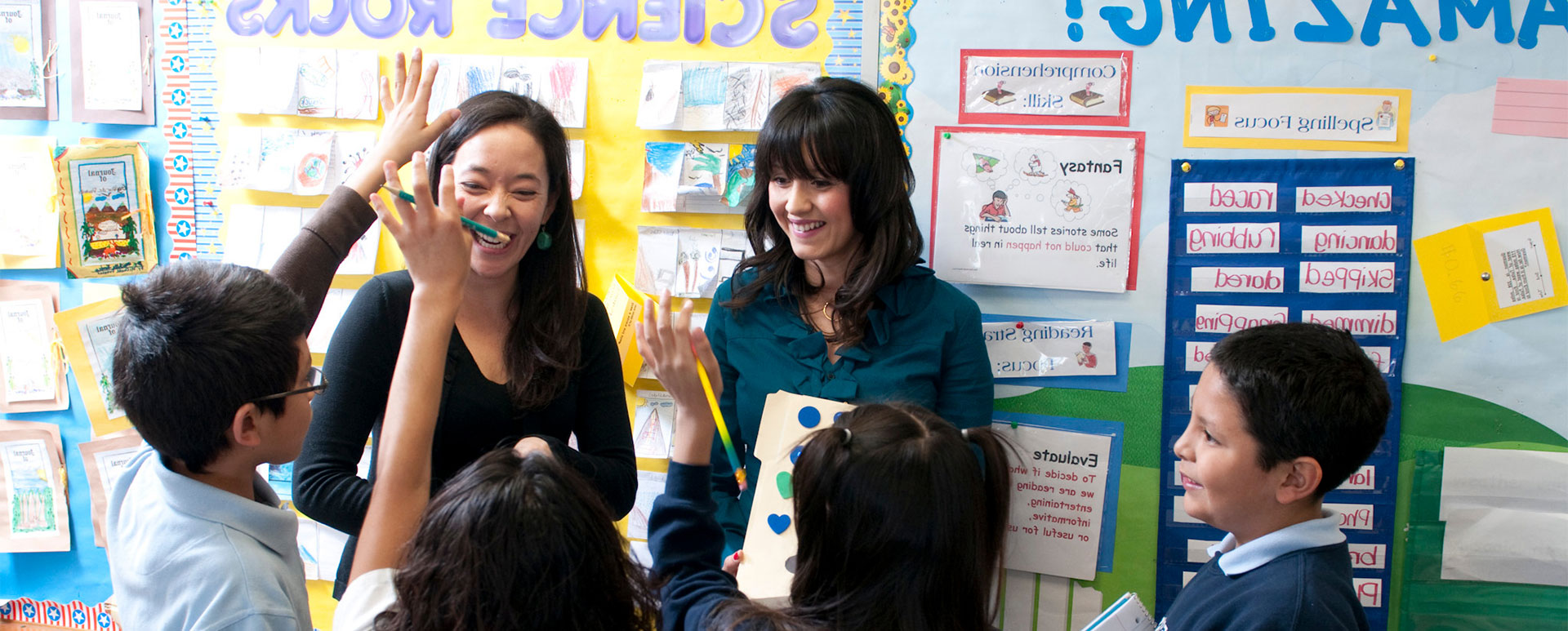 Two female teachers working with school age children in a classroom.